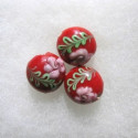 Red lamp-work coin bead with green and pink decoration.