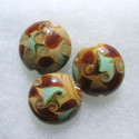 Brown and green art glass coin bead. Swirly design.