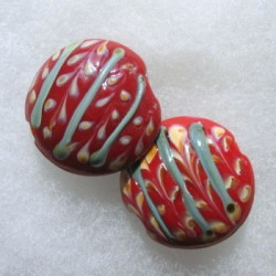 Red glass coin bead with green and cream decoration.