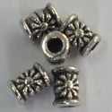 Small tubular bead, embossed flower design.
